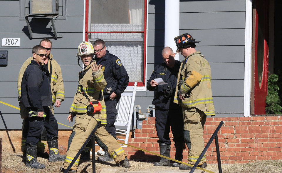 Photo -  Oklahoma City police and fire officials investigate the scene where a woman was found dead inside a burning duplex. [Photo by Paul Hellstern, The Oklahoman]