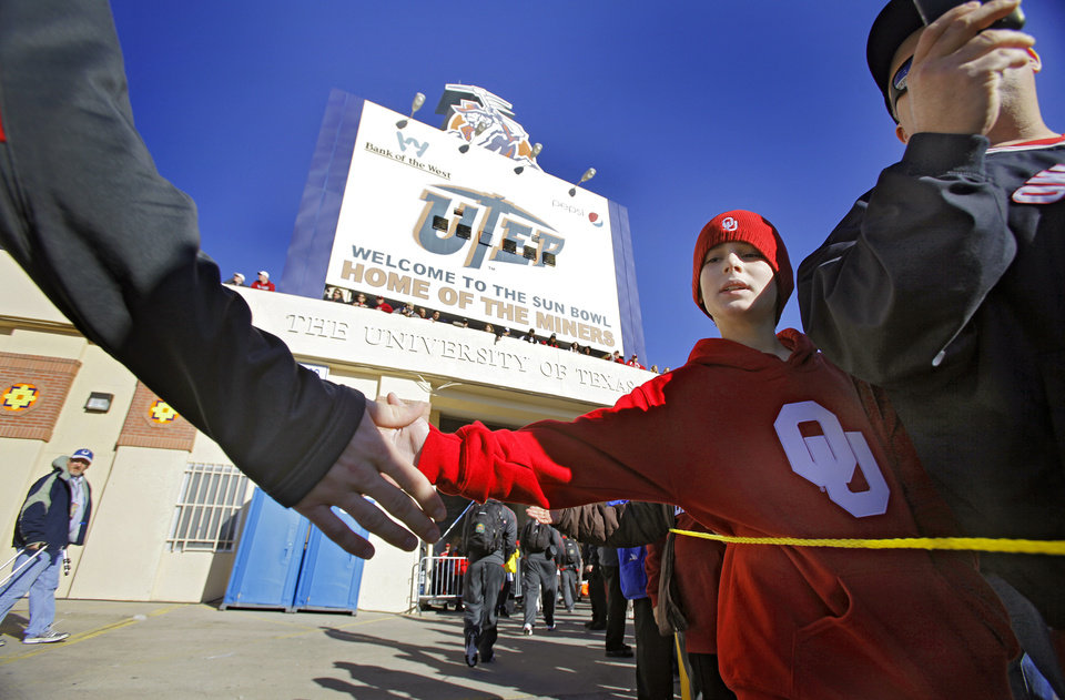 Photo - Matthew Randolph, of Edmond, slaps hands with the Sooners as the team arrives to the Brut Sun Bowl college football game between the University of Oklahoma Sooners (OU) and the Stanford University Cardinal on Thursday, Dec. 31, 2009, in El Paso, Tex.   Photo by Chris Landsberger, The Oklahoman