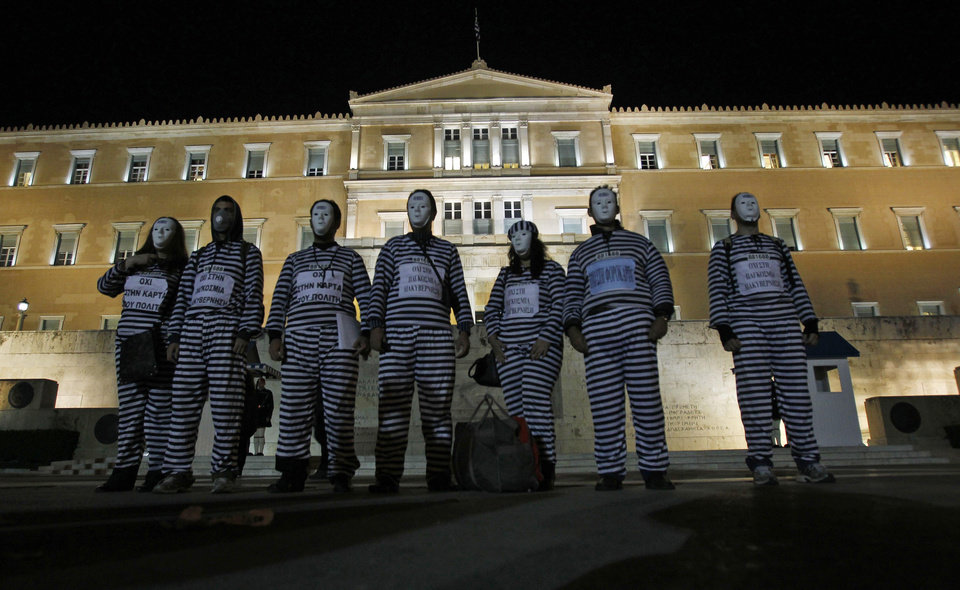 "Protesters dressed as prisoners gather during an event to protest against austerity measures outside the Greek parliament in Athens, Tuesday, Nov. 1, 2011. Lawmakers in Greece's ruling Socialist party revolted Tuesday over their prime minister's surprise decision to hold a referendum on a European debt deal, threatening the very survival of his embattled government. Writing on the uniforms read: 'No to new tax card' and ""No to global governance'.  (AP Photo/Thanassis Stavrakis) ORG XMIT: XTS112"