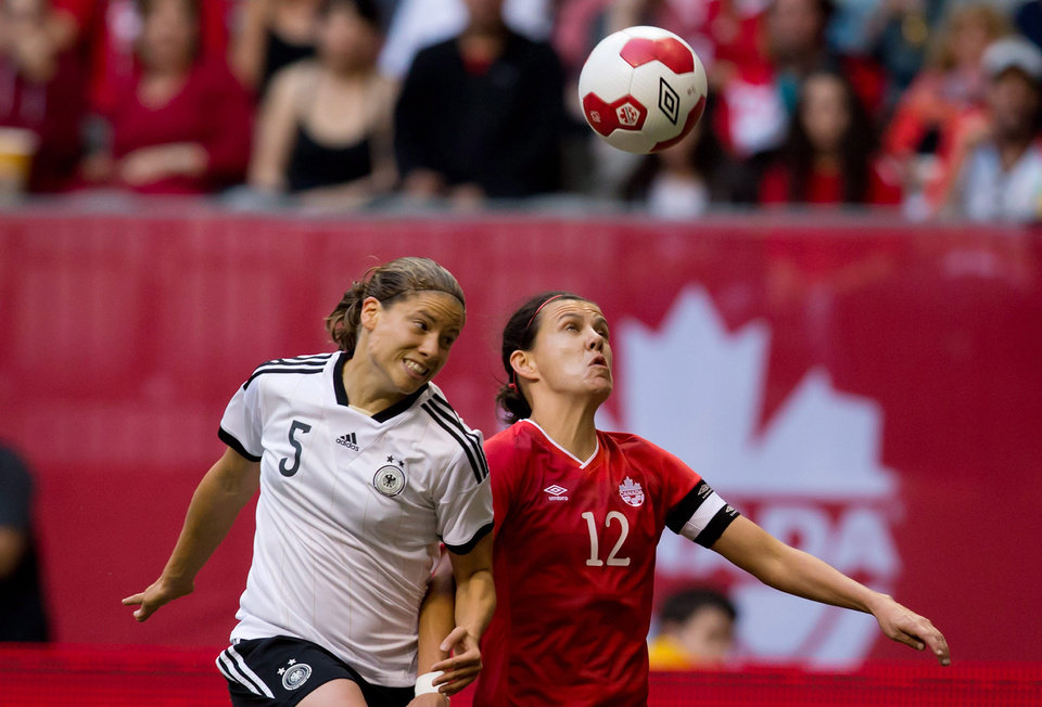 Photo - Germany's Annike Krahn, left, and Canada's Christine Sinclair vie for the ball during the first half of an international women's soccer game in Vancouver, British Columbia on Wednesday, June 18, 2014.  (AP Photo/The Canadian Press, Darryl Dyck)