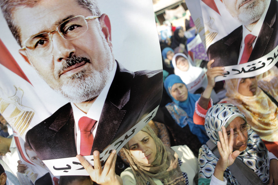 Photo - Supporters of ousted Egyptian President Mohammed Morsi hold posters with Morsi's face and words in Arabic that read