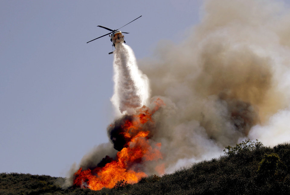 Photo - A helicopter makes a water drop on a hotspot over a hill near Thousand Oaks, Calif. on Thursday, May 2, 2013. Authorities have ordered evacuations of a neighborhood and a university about 50 miles west of Los Angeles where a wildfire is raging close to subdivisions. The blaze on the fringes of Camarillo and Thousand Oaks broke out Thursday morning and was quickly spread by gusty Santa Ana winds. Evacuation orders include California State University, Channel Islands. (AP Photo/Nick Ut)