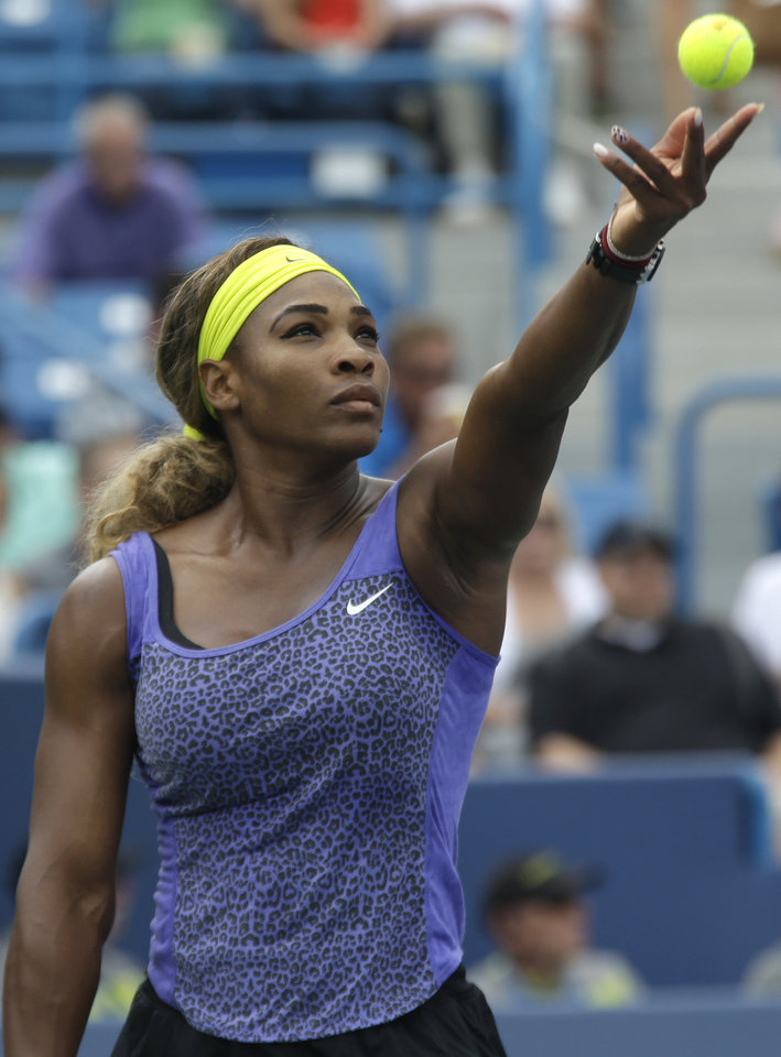 Photo - Serena Williams serves against Ana Ivanovic, from Serbia, during a final match at the Western & Southern Open tennis tournament, Sunday, Aug. 17, 2014, in Mason, Ohio. Williams won 6-4, 6-1. (AP Photo/Al Behrman)