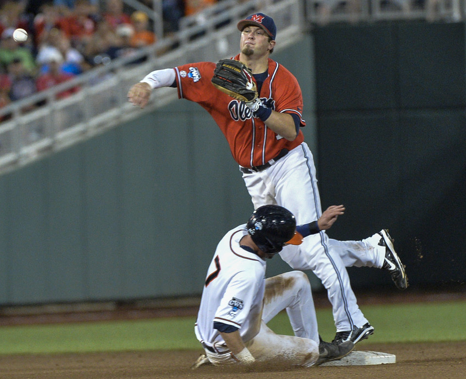 Photo - Mississippi second baseman Preston Overbey (1) throws to first after forcing out Virginia's Branden Cogswell (7) but does not complete a double play in the seventh inning of an NCAA baseball College World Series game in Omaha, Neb., Sunday, June 15, 2014. (AP Photo/Ted Kirk)