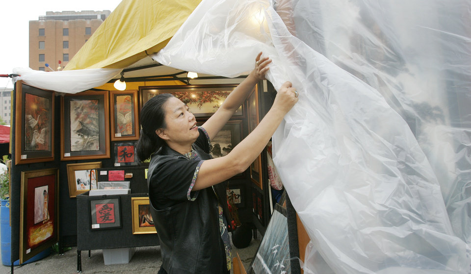 Artist Yong Qun Guo of Florida adjusts the covering at her booth as the threat of rain increased Wed. afternoon Apirl 23, 2008 at the Festival of the Arts in downtown Oklahoma City, OK. BY JACONNA AGUIRRE/THE OKLAHOMAN