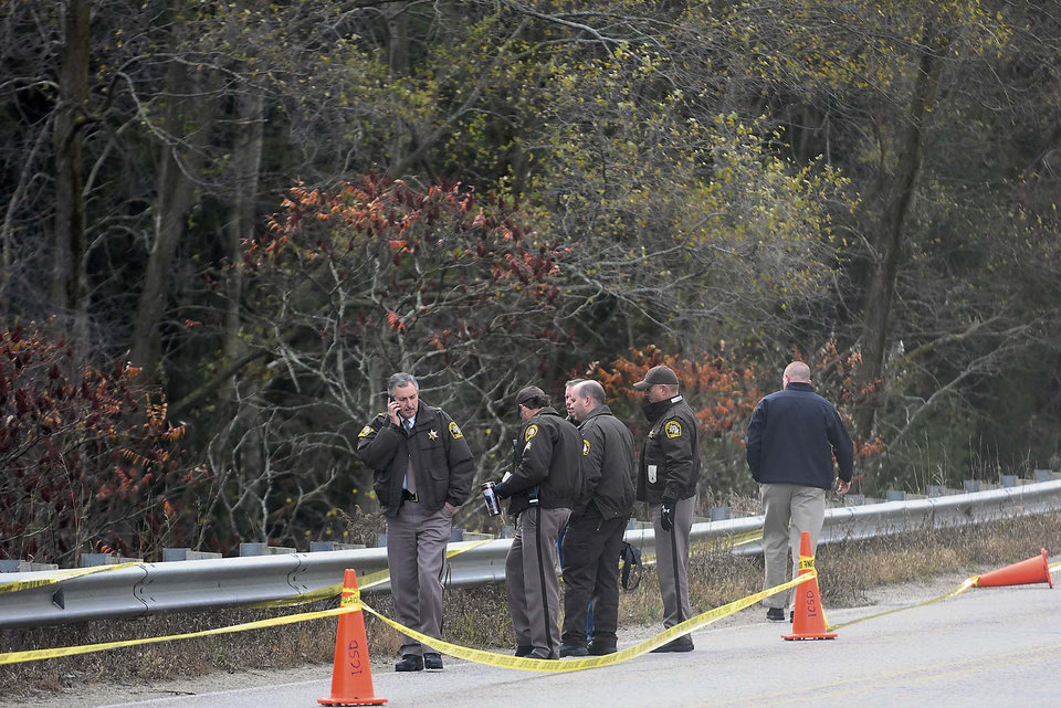 Police stand near a wooded area on the corner of Pickard and Coldwater west of Mount Pleasant, Mich. on Thursday, Nov. 1, 2012 where a female body was found. John D. White, a 55-year-old ex-convict has confessed to beating and strangling a 24-year-old neighbor as part of a sexual fantasy, hiding her naked body and then returning to her central Michigan trailer home and helping her 3-year-old son get costumed for Halloween, authorities said Thursday.(AP Photo/The Morning Sun, Lisa Yanick-Jonaitis)
