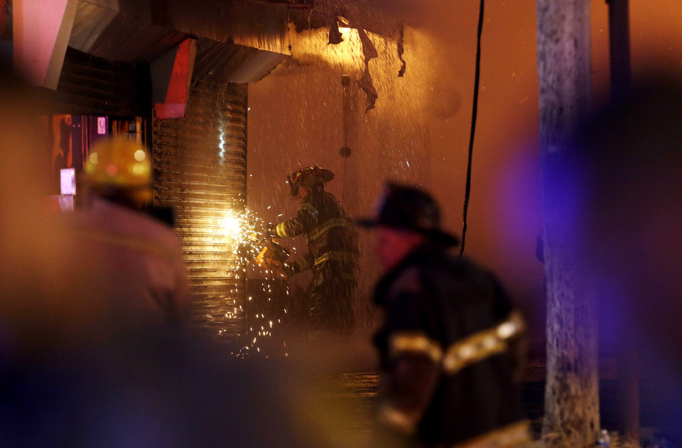 Photo - A firefighter saws through a metal wall on a building while battling a fire at the Seaside Park boardwalk on Thursday, Sept. 12, 2013, in Seaside Park, N.J. The fire began in a frozen custard stand on the Seaside Park section of the boardwalk and quickly spread north into neighboring Seaside Heights. (AP Photo/Julio Cortez)