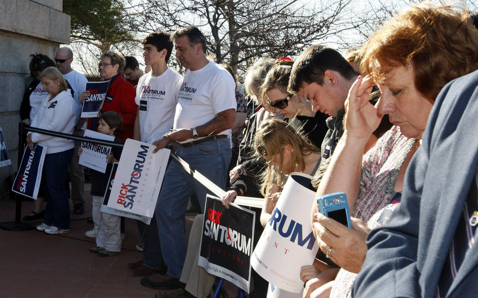 Photo - Supporters of Republican presidential candidate former Pennsylvania Sen. Rick Santorum bow their heads in prayer at the beginning of a rally in Oklahoma City, Sunday, March 4, 2012. (AP Photo/Sue Ogrocki) ORG XMIT: OKSO101