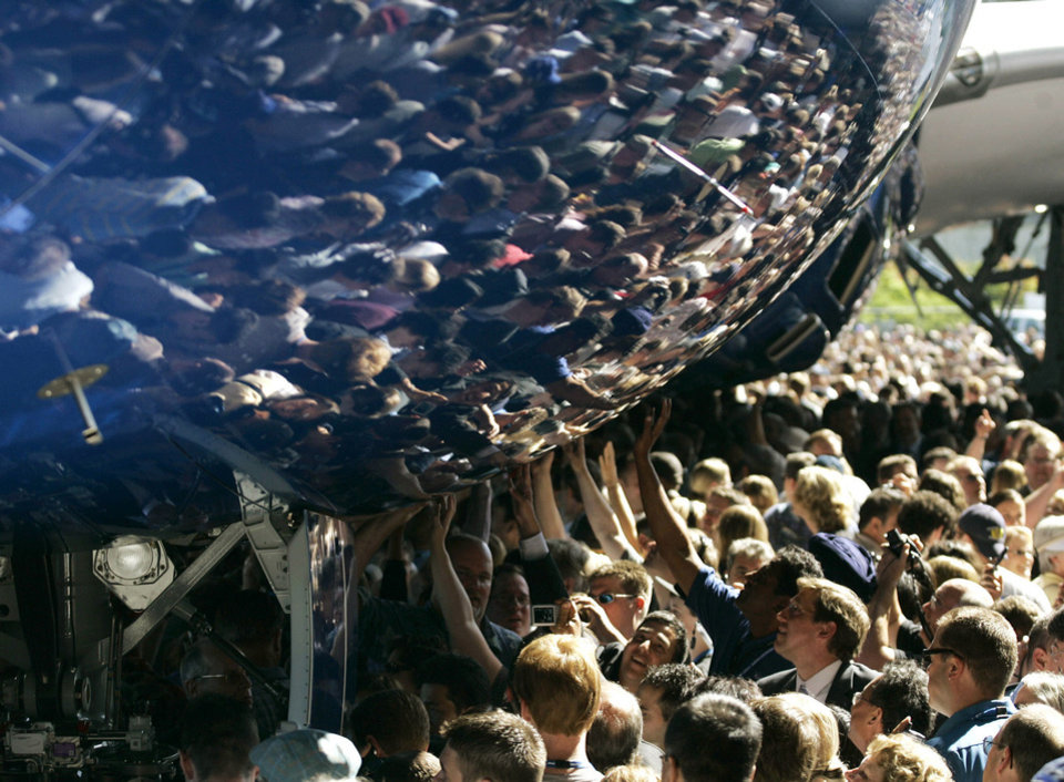 Visitors reach out to touch the fuselage of the first production model of the new Boeing 787 airplane July 8, 2007, after it was unveiled to an audience of several thousand at Boeing�s assembly plant in Everett, Wash.  AP Archives Photo
