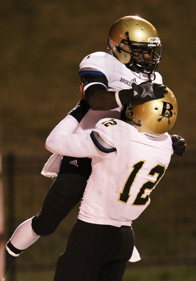 Photo - BA #12 Coleman Key lifts up #1 Austin Reed after he scored the first Tiger touchdown during the high school football game between Broken Arrow and Westmoore at Moore stadium Friday , November 8, 2013. Photo by Doug Hoke, The Oklahoman