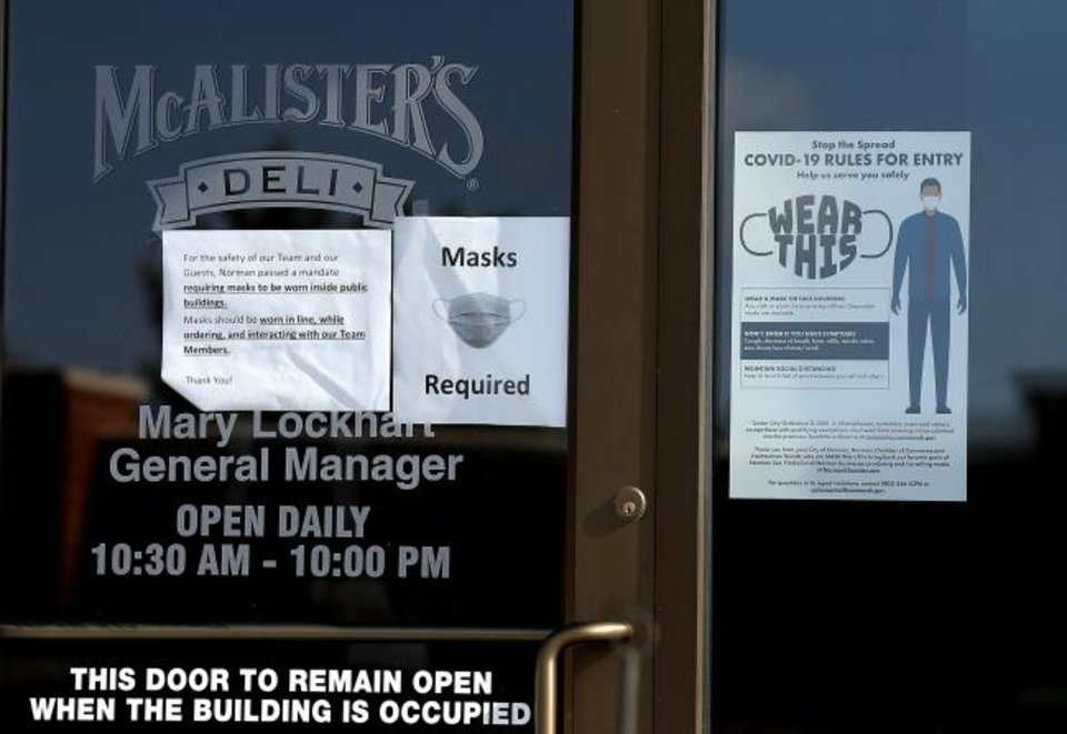 Photo -  A sign letting customers know masks are required hangs on the door of McAlister's Deli in Norman. [Sarah Phipps/The Oklahoman]