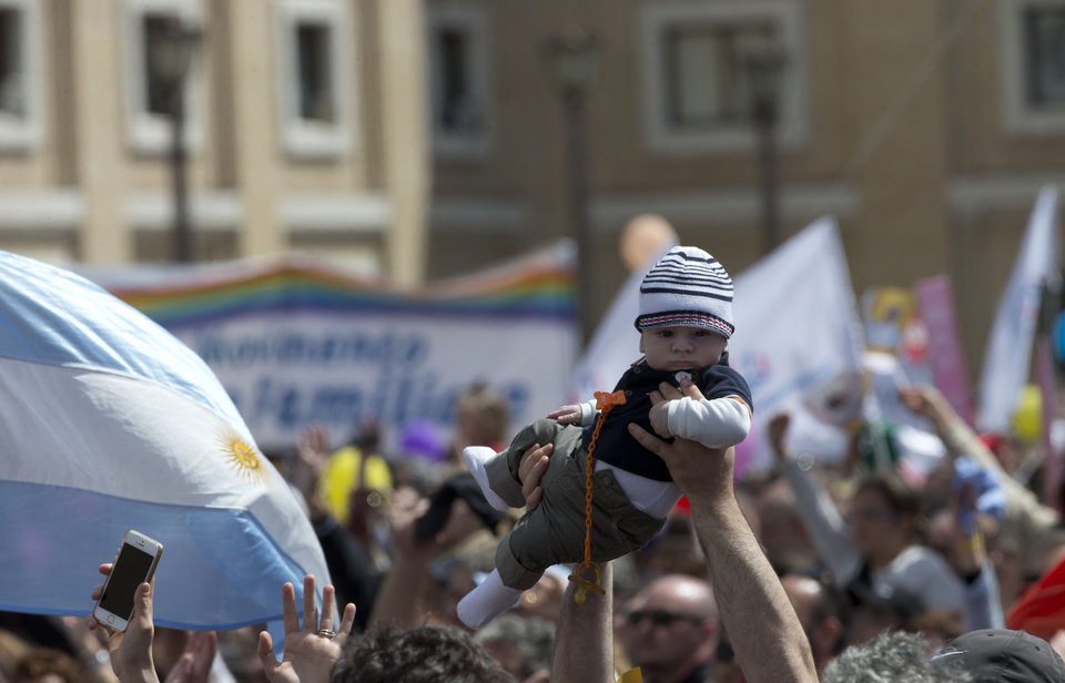 Photo - A man lifts a baby up as he waits for Pope Francis to recite the Regina Coeli prayer from the window of his studio overlooking St. Peter's Square, at the Vatican, Sunday, May 4, 2014. (AP Photo/Alessandra Tarantino)