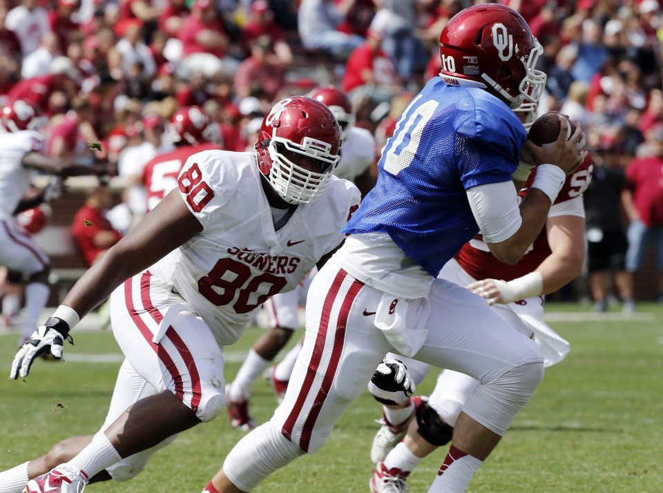 Jordan Phillips (80) pursues quarter back Blake Bell during the annual Spring Football Game at Gaylord Family-Oklahoma Memorial Stadium in Norman, Okla., on Saturday, April 13, 2013. Photo by Steve Sisney, The Oklahoman