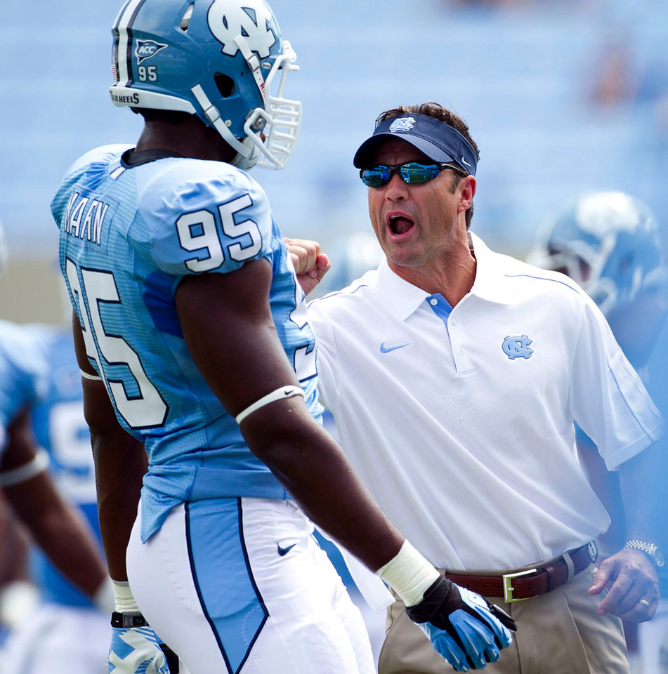 Photo -   North Carolina head coach Larry Fedora has a word with Kareem Martin (95) during the Tar Heels' pre-game warm up for their season-opening NCAA college football game against Elon, Saturday Sept. 1, 2012, at Kenan Stadium in Chapel Hill, N.C. (AP Photo/The News & Observer, Robert Willett) MANDATORY CREDIT