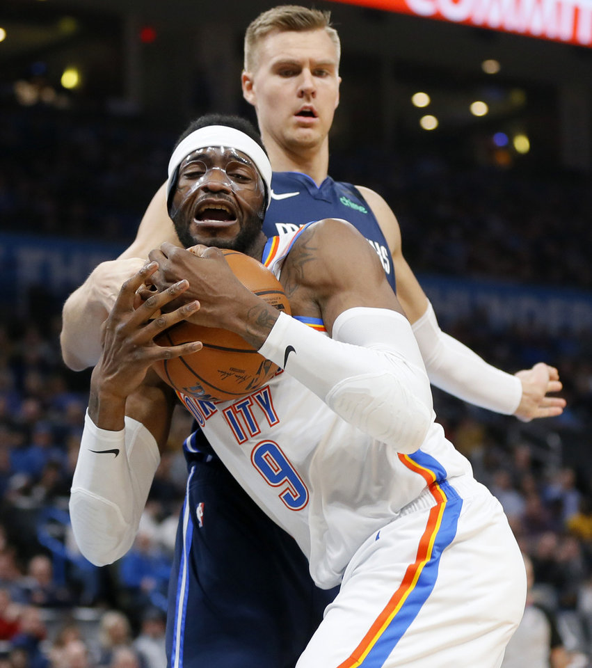 Photo - Oklahoma City's Nerlens Noel (9) secures a rebound in front of Dallas' Kristaps Porzingis (6) in the first quarter during an NBA basketball game between the Oklahoma City Thunder and Dallas Mavericks at Chesapeake Energy Arena in Oklahoma City, Monday, Jan. 27, 2020. [Nate Billings/The Oklahoman]