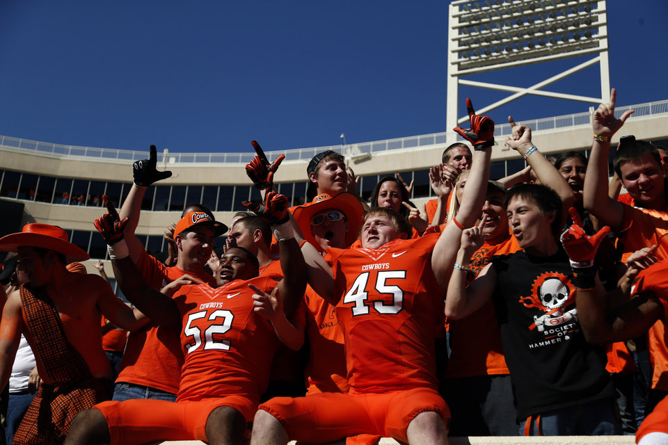 Oklahoma State\'s Ryan Simmons (52) and Caleb Lavey (45) celebrate with fans following a college football game between Oklahoma State University (OSU) and Iowa State University (ISU) at Boone Pickens Stadium in Stillwater, Okla., Saturday, Oct. 20, 2012. Photo by Sarah Phipps, The Oklahoman