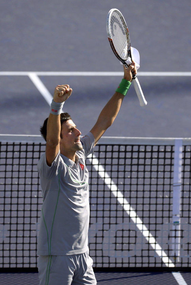 Photo - Novak Djokovic, of Serbia, celebrates on the court after he beat Roger Federer, of Switzerland, 3-6, 6-3, 7-6 to win the final match of the BNP Paribas Open tennis tournament, Sunday, March 16, 2014, in Indian Wells, Calif. (AP Photo/Mark J. Terrill)