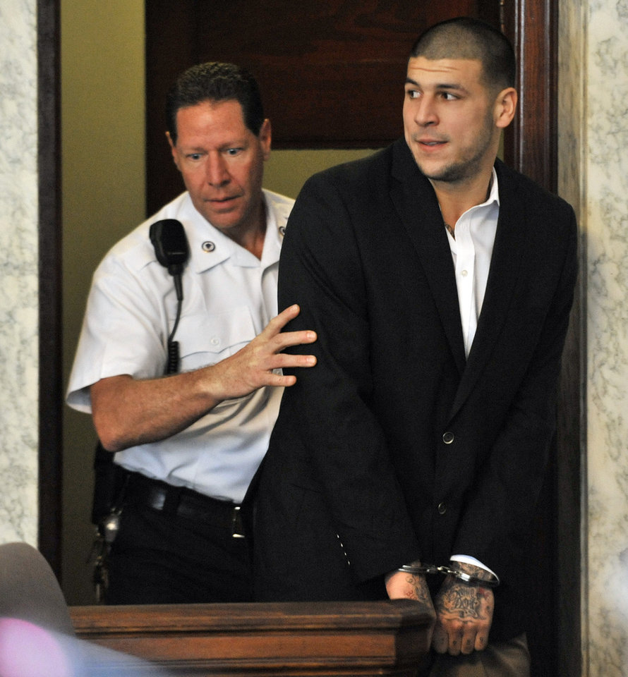 Photo - ADVANCE FOR WEEKEND EDITIONS, AUG 24-25 - Former New England Patriot football player Aaron Hernandez, is lead into court in Attleboro, Mass., Thursday, Aug. 22, 2013, where je was indicted on first-degree murder and weapons charges in the death of a friend whose bullet-riddled body was found in an industrial park about a mile from the ex-player's home. The NFL never really shuts down. It kept rolling long after the lights came back on after a 37-minute delay at the Super Bowl, right into a new season that will kick off in less than two weeks and end with an outdoor Super Bowl in New Jersey.  In between, there were plenty of headlines. (AP Photo/Josh Reynolds)
