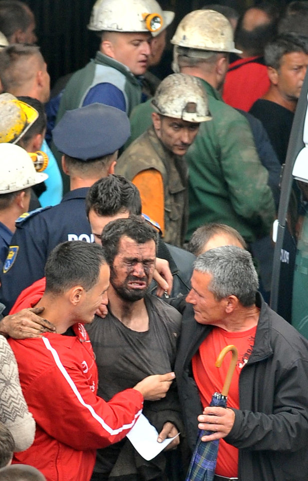 Photo - Rescuers help a miner who was trapped in the Raspotocje coal mine in Zenica,70 km north of Sarajevo, Bosnia, Friday, Sept. 5, 2014. Rescuers on Friday were pulling out some of the 34 miners who had been trapped deep inside a coal mine that collapsed in central Bosnia. Tired, their faces smeared with coal dust, the men came out of the Zenica mine one by one, after spending the night more than 500 meters (1,600 feet) below the ground. (AP Photo/Amel Emric)