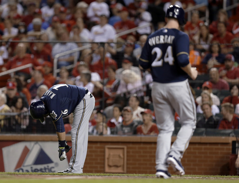 Photo - Milwaukee Brewers' Lyle Overbay, right, jogs in to score the tying run after Aramis Ramirez, left, was hit by a pitch with the bases loaded during the seventh inning of a baseball game against the St. Louis Cardinals on Monday, April 28, 2014, in St. Louis. (AP Photo/Jeff Roberson)