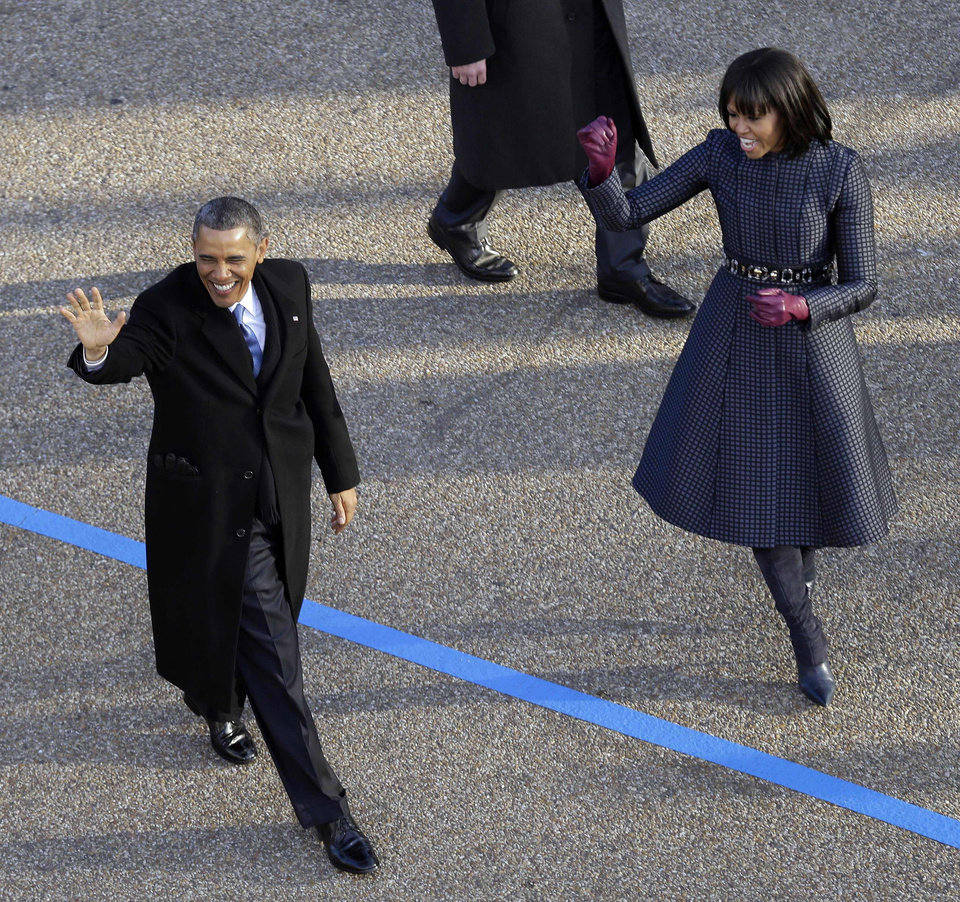 Photo - President Barack Obama and first lady Michelle Obama walk the inaugural parade route down Pennsylvania Avenue en route to the White House, Monday, Jan. 21, 2013, in Washington. Thousands  marched during the 57th Presidential Inauguration parade after the ceremonial swearing-in of President Barack Obama. (AP Photo/Charlie Neibergall)