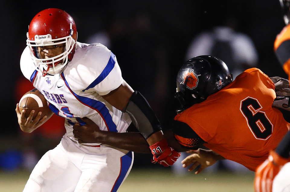 Photo - John Marshall's Devonte Lee runs past Douglass' Raymond Alexander during the  All-City Preview football scrimmages at Douglass High School in Oklahoma City, Friday, August 29, 2014. Photo by Bryan Terry, The Oklahoman