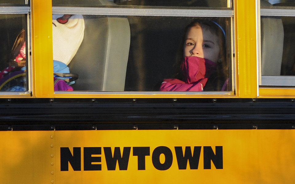 A girl sits on a Newtown bus leaving the new Sandy Hook Elementary School after the first day of classes in Monroe, Conn., Thursday, Jan. 3, 2013. The Sandy Hook students started today in a new school, formerly called Chalk Hill School in Monroe. It was renamed Sandy Hook Elementary and overhauled especially for the students from the Sandy Hook School shooting. (AP Photo/Jessica Hill) (AP Photo/Jessica Hill)