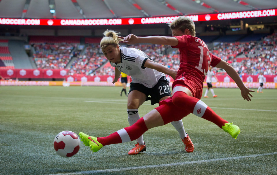 Photo - Germany's Luisa Wensing, left, forces Canada's Sophie Schmidt off the ball during the first half of an international women's soccer game in Vancouver, British Columbia on Wednesday, June 18, 2014.  (AP Photo/The Canadian Press, Darryl Dyck)