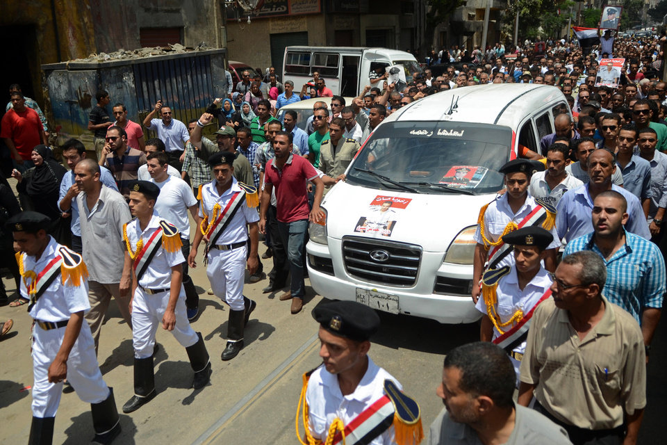 Photo - Egyptian policemen march with a vehicle carrying the body of their comrade, killed Monday in Cairo outside of the Republican Guard headquarters in an incident that left 51 people dead, at his funeral in Alexandria, Egypt, Tuesday, July 9, 2013. The shootings began during a protest by about 1,000 Islamists outside the Republican Guard headquarters where Morsi, Egypt's first freely elected leader, was detained last week. Demonstrators and members of the Brotherhood said troops descended on them and opened fire unprovoked as they finished dawn prayers. (AP Photo/Tarek Elframawy)