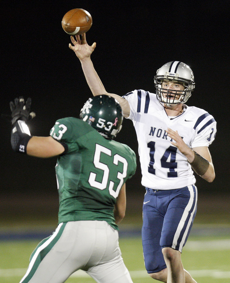 Photo - Edmond Santa Fe's Josh Crouch (53) defends a pass by Jesse Mathews (14) of Edmond North during a high school football game between Edmond Santa Fe and Edmond North at Wantland Stadium in Edmond, Okla., Friday, Oct. 28, 2011. Photo by Nate Billings, The Oklahoman