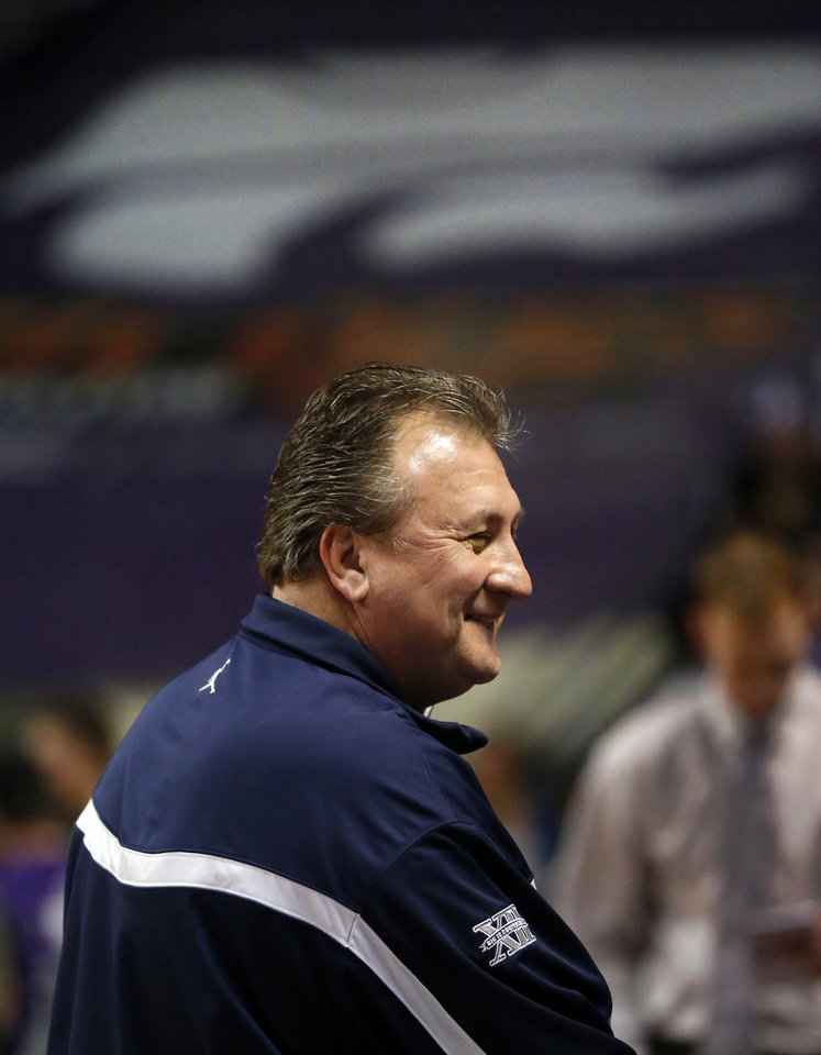 Photo - West Virginia head coach Bob Huggins smiles while talking with fans during warmups before an NCAA college basketball game against Kansas State in Manhattan, Kan., Monday, Feb. 18, 2013. Monday's game marked Huggins' first return to Bramlage Coliseum after coaching Kansas State for one year. (AP Photo/Orlin Wagner)