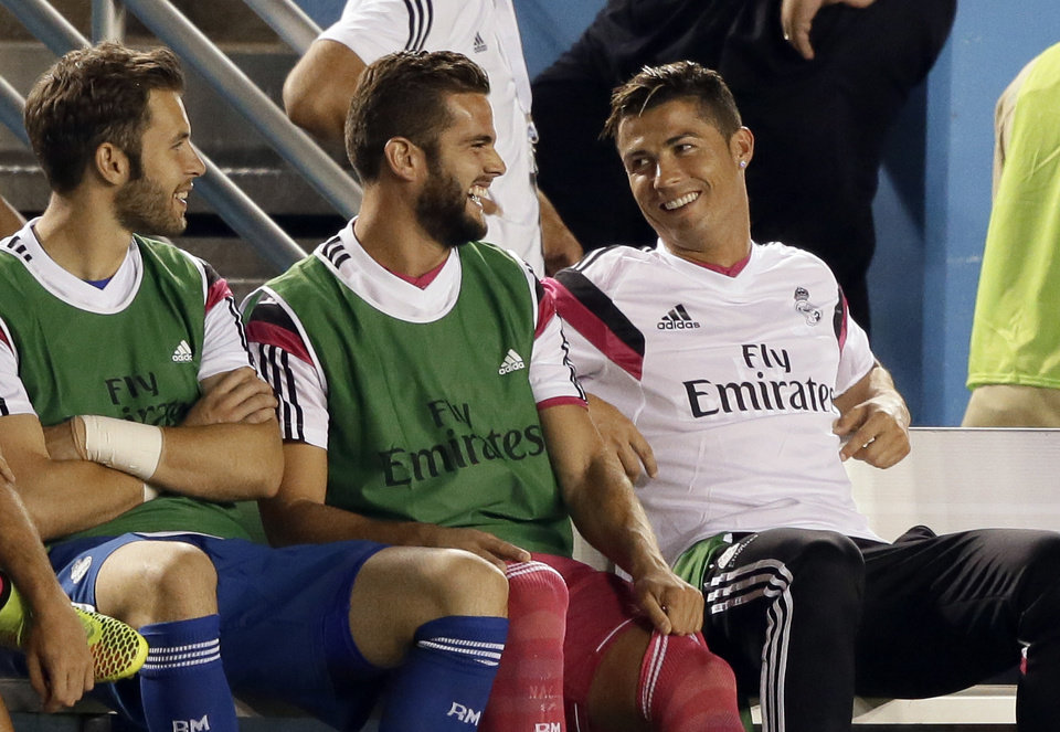 Photo - Real Madrid's Cristiano Ronaldo, right, smiles as he talks with teammates on the bench in the first half of a Guinness International Champions Cup soccer tournament match, Tuesday, July 29, 2014, in Dallas. (AP Photo/Tony Gutierrez)