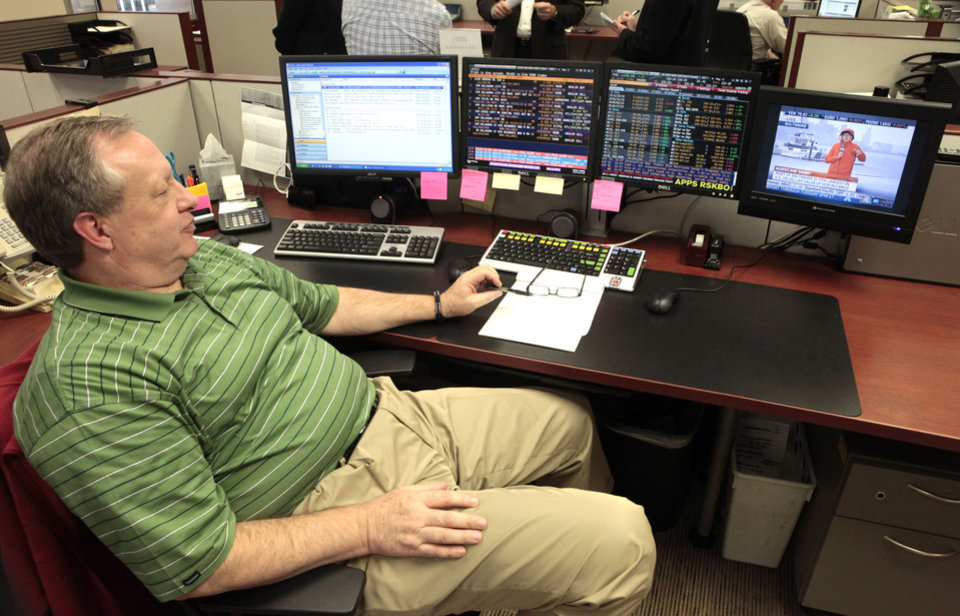 Jim McIntyre, vice president  of institutional investments for BOSC,  watches hurricane coverage in the trading room at the Oklahoma City firm's office Monday. All stock trading was  closed Monday, but the room is staffed. Photo By David McDaniel, The Oklahoman <strong>David McDaniel - The Oklahoman</strong>