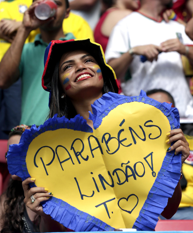 Photo - A Colombian supporter holds a sign saying 'Congratulations Handsome' before the group C World Cup soccer match between Colombia and Ivory Coast at the Estadio Nacional in Brasilia, Brazil, Thursday, June 19, 2014. (AP Photo/Marcio Jose Sanchez)