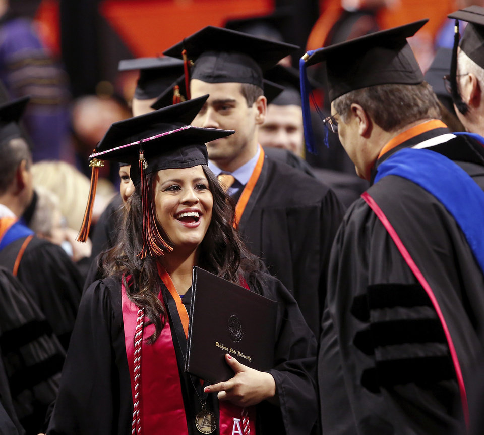 A graduate  smiles while being congratulated by university faculty representatives as she returns to her seat after walking across the stage. Undergraduates at OSU participated in the school's 127th commencement ceremony the weekend of Friday, May 3 and Saturday, May 4, 2013 inside Gallagher-Iba Arena on the university's campus.These photos were taken at the Saturday morning ceremony when students from the College of Agricultural Sciences and Natural Resources, and the Spears School of Business were conferred with degrees.   Photo  by Jim Beckel, The Oklahoman.