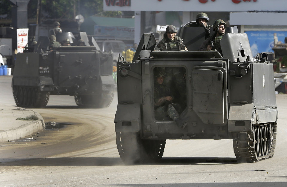 Lebanese army soldiers patrol in armored vehicles after clashes erupted between pro and anti-Syrian regime gunmen in the northern port city of Tripoli, Lebanon, Wednesday, Dec. 5, 2012. Gunmen loyal to opposite sides in neighboring Syria's civil war battled in the streets of northern Lebanon at a time of deep uncertainty in Syria, with rebels closing in on President Bashar Assad's seat of power in Damascus. (AP Photo/Hussein Malla)