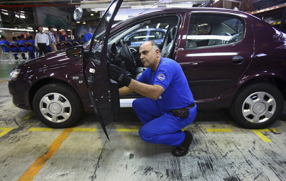 Photo - Iranian car worker Alireza Fazel inspects a car before it's exported to Russia for the first time since 2009, at the state-run Iran-Khodro automobile manufacturing plant near Tehran, Iran, Sunday, June 29, 2014. Iran began exporting automobiles to Russia for the first time in five years on Sunday, after meeting upgraded emission standards, the country's largest auto manufacturer said. (AP Photo/Vahid Salemi)