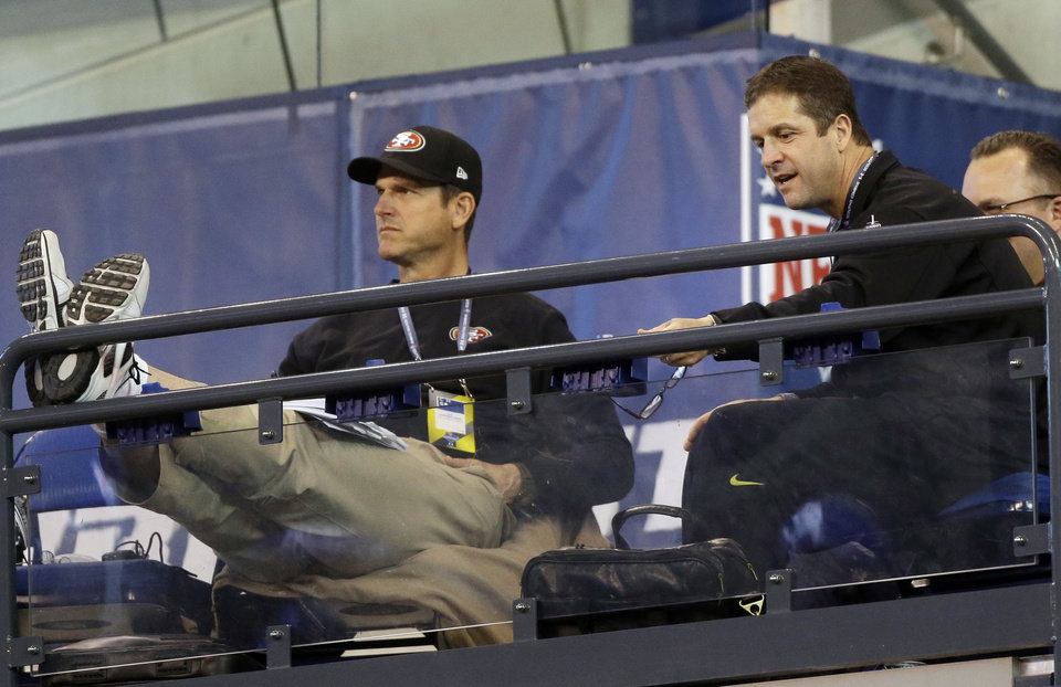 San Francisco 49ers coach Jim Harbaugh, left, and his brother, Baltimore Ravens coach John Harbaugh watch from the stands as players run a drill during the NFL football scouting combine in Indianapolis, Saturday, Feb. 23, 2013. (AP Photo/Dave Martin)