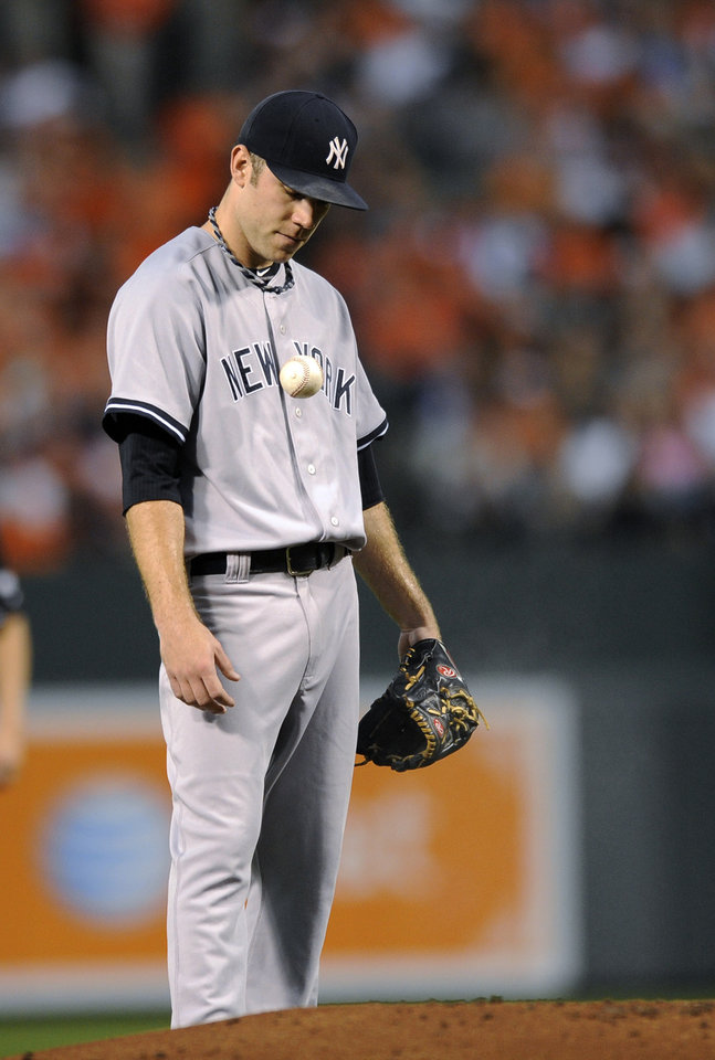 Photo -   New York Yankees starting pitcher David Phelps reacts after he was called for a balk during the first inning of a baseball game against the New York Yankees, Thursday, Sept. 6, 2012, in Baltimore. (AP Photo/Nick Wass)