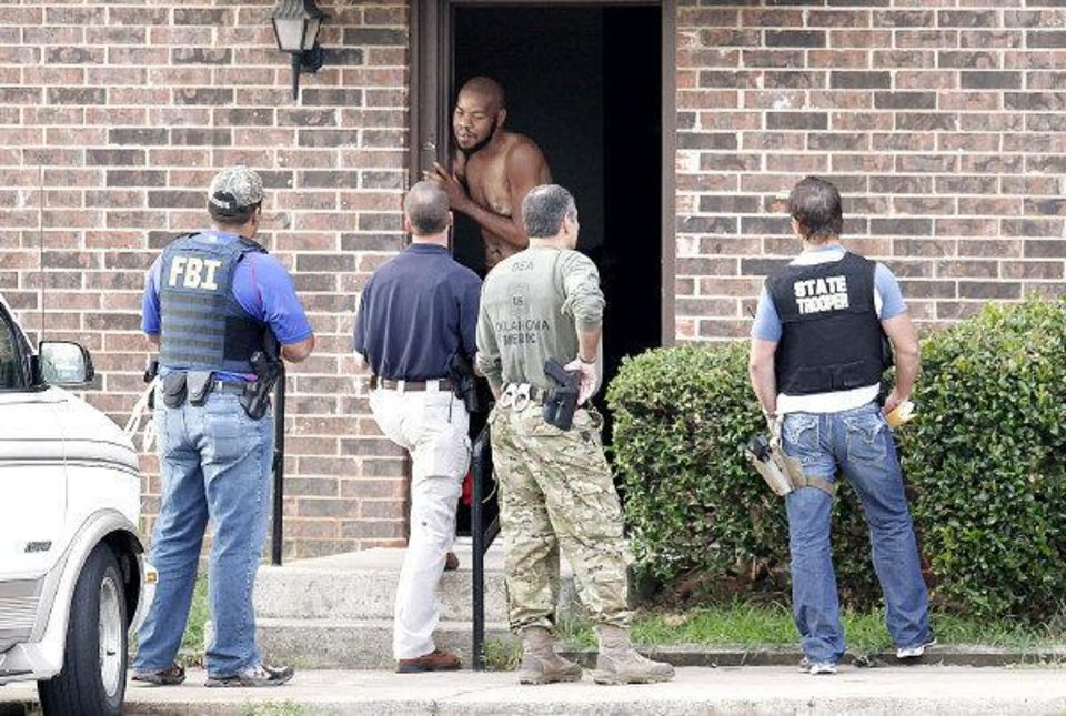 Agents with the Edmond Police Department, the FBI and the Oklahoma Highway Patrol go door-to-door asking residents questions as they execute drug search warrants at the Rolling Green Apartments in Edmond. PHOTO BY PAUL B. SOUTHERLAND, THE OKLAHOMAN PAUL B. SOUTHERLAND
