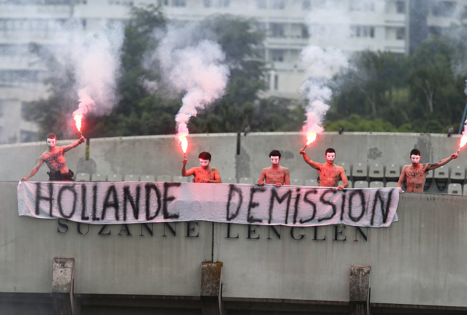 Photo - Demonstrators display a banner demanding the resignation of French President  Francois Hollande, atop Suzanne Lenglen court, as Spain's Rafael Nadal plays compatriot David Ferrer on center court during the men's final match of the French Open tennis tournament at the Roland Garros stadium Sunday, June 9, 2013 in Paris. (AP Photo/David Vincent)