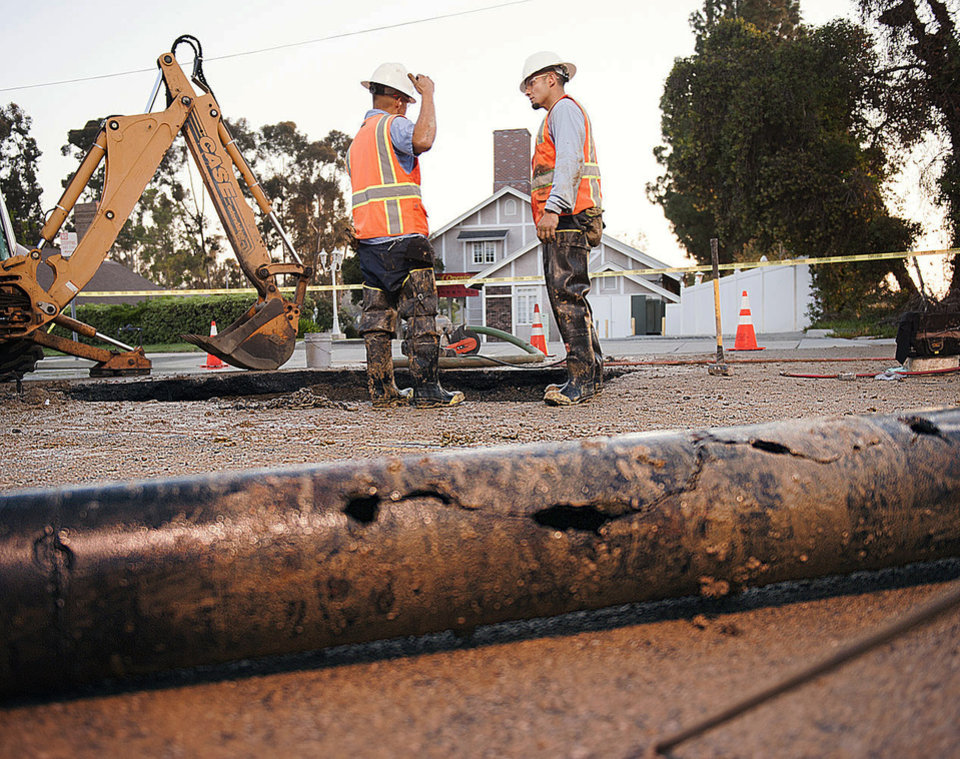 Photo - City of Fullerton maintenance workers Eric Becerra, left, and Ernie Vejar wait for a new section of pipe to be cut early Saturday, March 29, 2014 in Fullerton, Calif.  More than 100 aftershocks have rattled Orange County south of Los Angeles where a magnitude-5.1 earthquake struck Friday.  Despite the relatively minor damage, no injuries have been reported. (AP Photo/The Orange County Register, Ken Steinhardt)   MAGS OUT; LOS ANGELES TIMES OUT