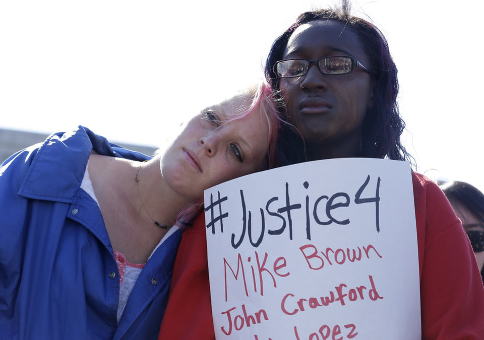Photo - Savannah McCoy, 17, right, holds up a sign as she and her friend Kimber Camgros, 16, listen to speakers during a vigil for Michael Brown of Ferguson, Mo., in San Francisco, Thursday, Aug. 14, 2014. Brown, an unarmed black teenager, was killed by a white police officer on Saturday, Aug. 9, 2014. (AP Photo/Jeff Chiu)