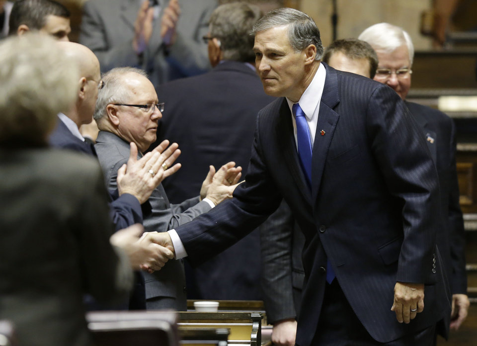 Washington Gov. Jay Inslee shakes hands with lawmakers in the House chamber, Wednesday, Jan. 16, 2013, after he spoke to a joint session of the Washington Legislature shortly after being sworn in as Governor, at the Capitol in Olympia, Wash. (AP Photo/Ted S. Warren)