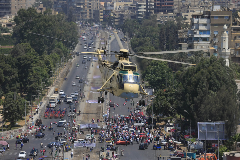 Photo - An Egyptian military helicopter flies over Egyptians protesting against the ousted President Mohammed Morsi during a demonstration at the presidential palace in Cairo, Egypt, Friday, July 26, 2013. Political allies of Egypt's military lined up behind its call for huge rallies Friday to show support for the country's top general, Abdel-Fattah el-Sissi, pushing toward a collision with Islamist opponents demanding the return of Mohammed Morsi, the nation's ousted president. (AP Photo/Hassan Ammar)