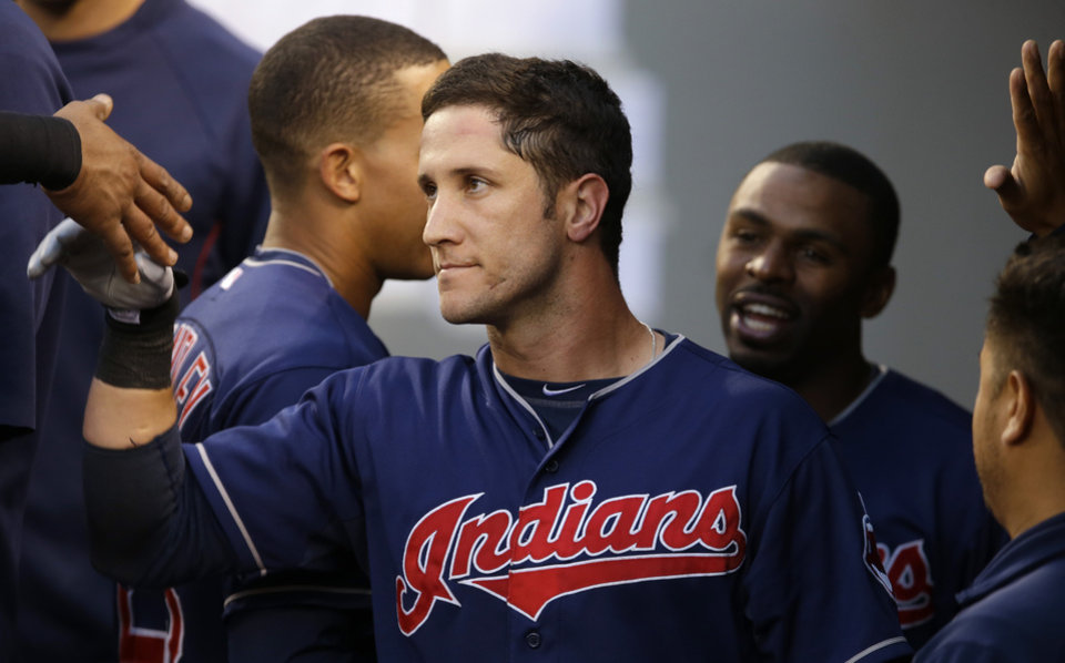 Photo - Cleveland Indians' Yan Gomes, center, is greeted in the dugout after he hit a solo home run against the Seattle Mariners in the sixth inning of a baseball game, Saturday, June 28, 2014, in Seattle. (AP Photo/Ted S. Warren)