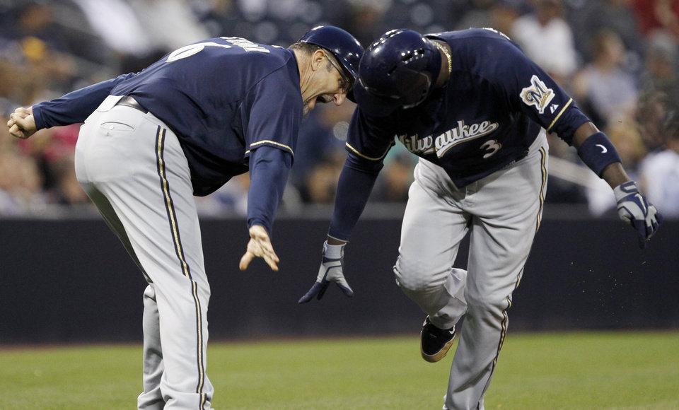 Milwaukee Brewers third base coach Ed Sedar, left, low-fives Yuniesky Betancourt (3) after Betancourt hit a three-run home run in the first inning of a baseball game against the San Diego Padres, Monday, April 22, 2013, in San Diego. (AP Photo/Alex Gallardo)