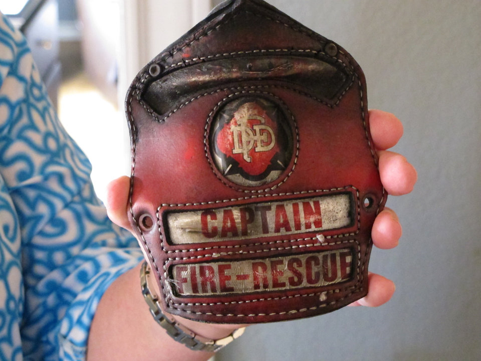 Photo - In this April 9, 2014 photo Holly Harris holds a badge that belonged to her husband, Dallas Fire-Rescue Capt. Kenneth Luckey Harris, at her home outside West, Texas. Kenneth Harris was one of 15 people killed in a deadly explosion at West Fertilizer Co., that still raises questions in the community one year later about what happened. (AP Photo/Nomaan Merchant)