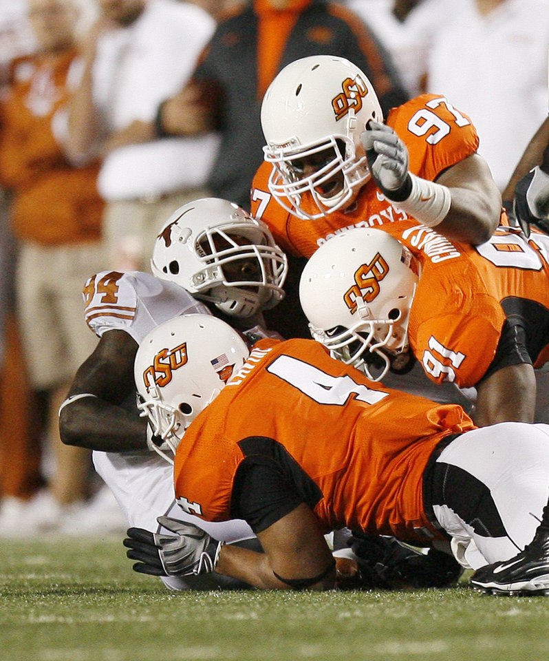Photo - Cowboys Jermiah Price (97), Ugo Chinasa (91) and Patrick Lavine (4) wrap up Marquise Goodwin (84)of Texas during the college football game between the Oklahoma State University Cowboys (OSU) and the University of Texas Longhorns (UT) at Boone Pickens Stadium in Stillwater, Okla., Saturday, Oct. 31, 2009. Photo by Sarah Phipps, The Oklahoman