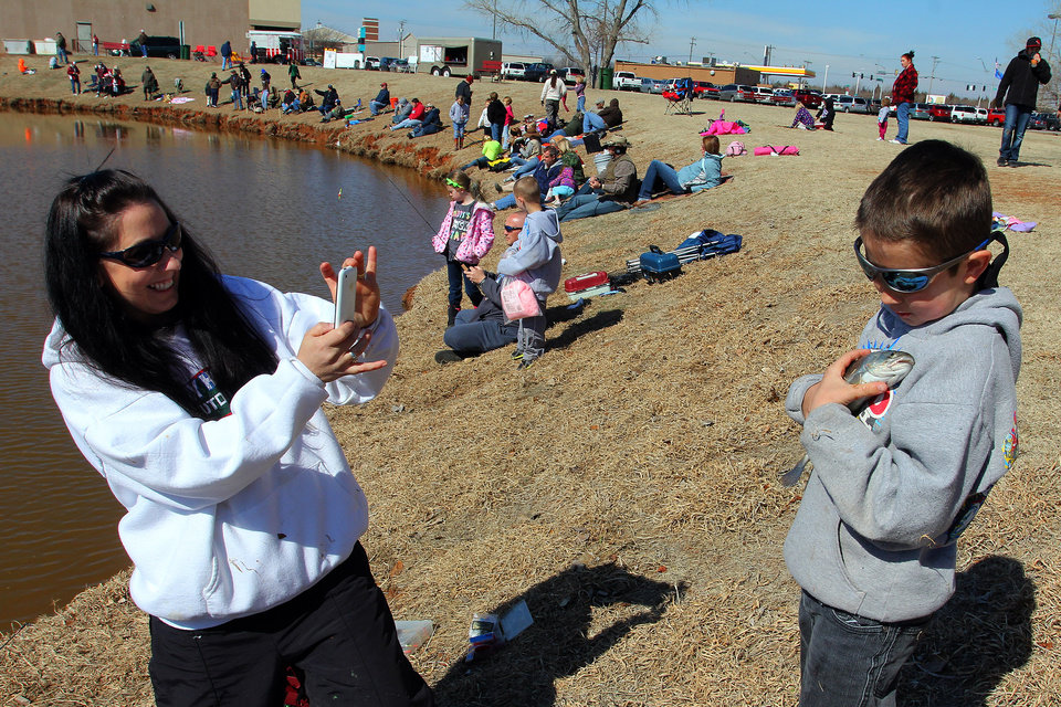 Wendy Ogden takes a picture of her son Hunter, 10, of Yukon as he holds his first catch of the day during the Trout Fish Out Saturday, March 2, 2013,  morning at the Dale Robertson Activity Center pond in Yukon. PHOTO BY HUGH SCOTT FOR THE OKLAHOMAN